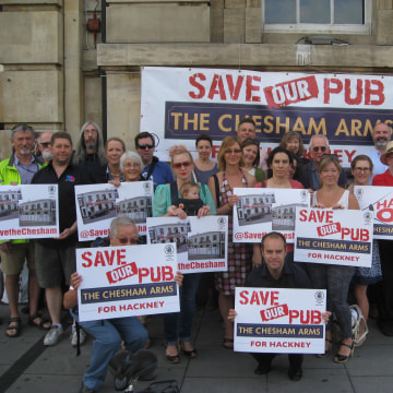 Image: Members of Save The Chesham, a neighborhood group in London fighting to have their local pub re-opened, show off their signs of protest.