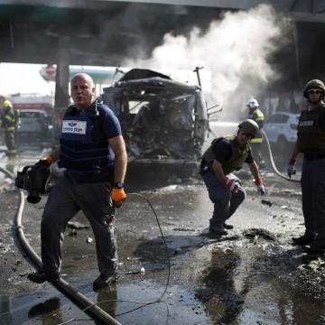 Image: Israeli police explosive experts survey the scene at a petrol station after it was hit by a rocket in Ashdod