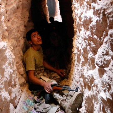 Image: A Free Syrian Army fighter sits inside a tunnel in the southern part of Maarat Al-Nouman, Idlib