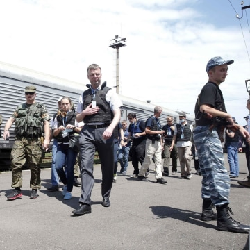 Image: Monitors walk near a train reportedly containing MH17 victims in Torez, Ukraine