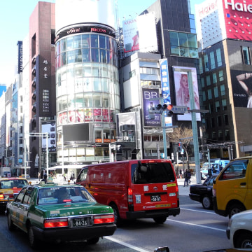 Image: A woman comes out of Ginza metro station as a taxi passes by in downtown Tokyo on March 17, 2011.
