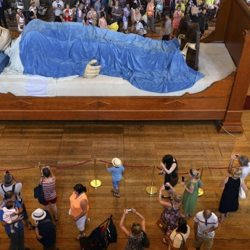 Image: Visitors look at a giant puppet of a grandmother sleeping on a bed in Liverpool