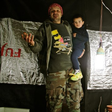 Image: Grower of the future? Alvaro Calistro, holding his young son, shows off his indoor marijuana plants