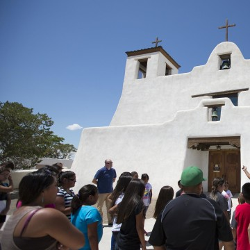 Image: Isleta Tribal Elder Max Zuni addresses students in front of the St. Augustine Church about their history and the importance of maintaining their native language.