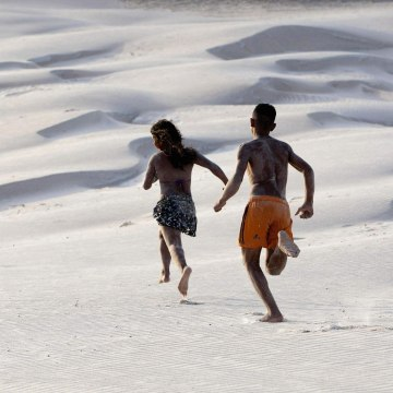 Image: Youths run along sand dunes during the peak of the summer vacation season on Atalaia beach in Salinopolis
