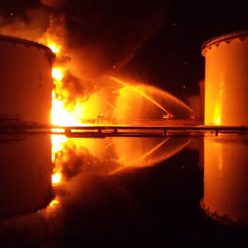 Image: Libyan firefighters dousing a huge blaze at an oil tank