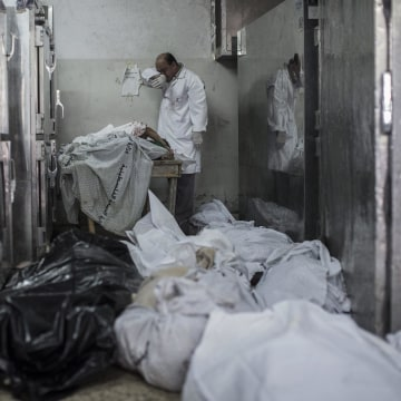 Image: A doctor cries while standing next to a table with the bodies of four dead children