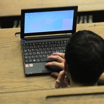 Image: A students works with his computer attending a lecture in an auditorium