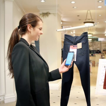 Image: A woman demonstrates Hointer's shopping technology.