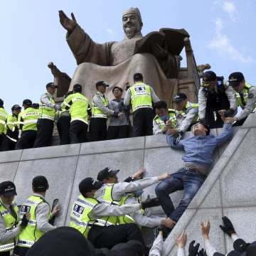 Image: Policemen detain university students on a statue of King Sejong the Great during a protest against South Korean President Park Geun-hye, in central Seoul