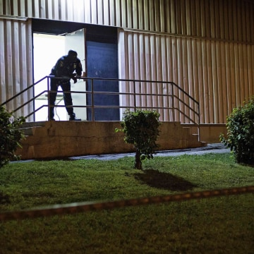 Image: A police officer stands at the door of a community recreation center during a curfew law in Baltimore