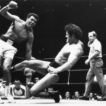 Japanese pro wrestler Antonio Inoki kicks the back of Muhammad Ali's leg