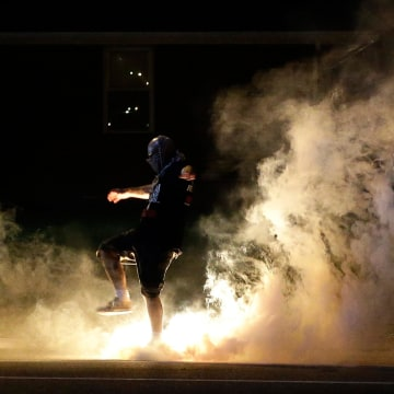 Image: A protester kicks a smoke grenade in Ferguson, Missouri