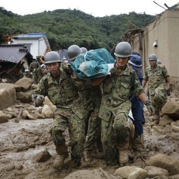Image: JSDF soldiers and police officers carry the body of a victim in a plastic bag at a site where a landslide swept through a residential area at Asaminami ward in Hiroshima