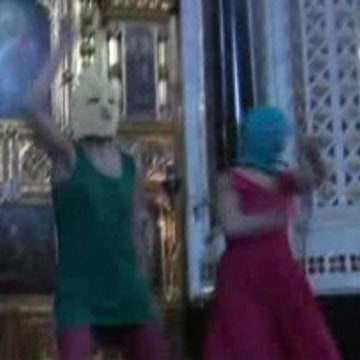 """Image: Still image taken from file video shows members of the female punk band """"Pussy Riot"""" staging a protest inside Christ The Saviour Cathedral in Moscow"""