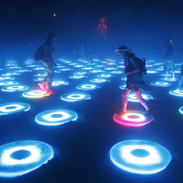 """Image: Participants interact with the art installation The Super Pool during a dust storm at the Burning Man 2014 """"Caravansary"""" arts and music festival in the Black Rock Desert of Nevada"""