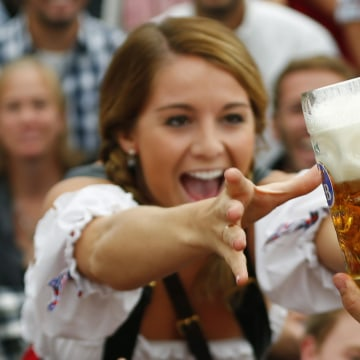 Image: A visitor reaches for a mug of beer during Oktoberfest's opening ceremony on Sept. 21, 2013