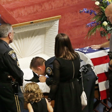 Image: Oklahoma City police officer Sgt. Ryan Stark, center, leans over the casket of his canine partner