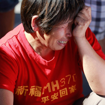 Image: A family member of passengers onboard the missing Malaysia Airlines Flight MH370 cry as they gather to pray Yonghegong Lama Temple in Beijing
