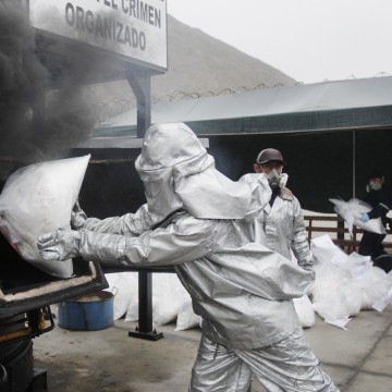 Image: Anti-narcotics officers burn bags of the cocaine seized last week near Trujillo at a special operation police headquarters, in Lima