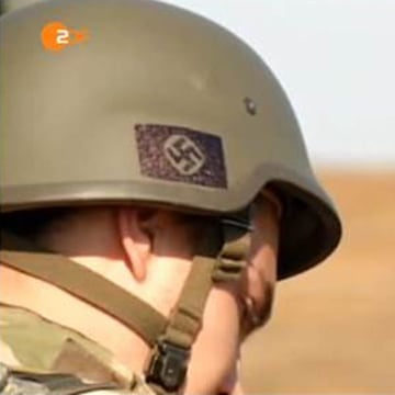 Ukrainian soldiers with Nazi symbols on their helmets, including the swastika.