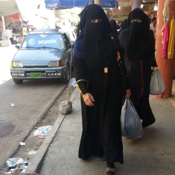 Image: Veiled Iraqi women walk along a street in the city of Mosul