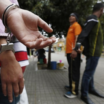 Image: Detainees, handcuffed to each other, stand at a public park in Bogota, Colombia