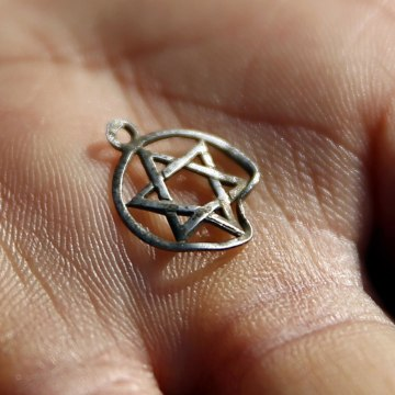 Image: A medallion in the shape of the Star of David is shown after being discovered in the perimeter of a Nazi death camp in Sobibor