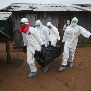 Image: A Liberian burial team wearing protective clothing retrieves the body of a 60-year-old Ebola victim
