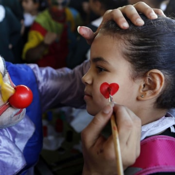 Image: A Palestinian clown paints the face of a student