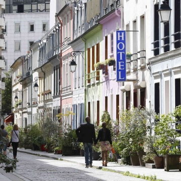 "Image: A view shows people walking rue Cremieux, a street lined with colorful, terraced homes, and the hotel ""L'Hotel Particulier"" located in the 12th district of Paris"