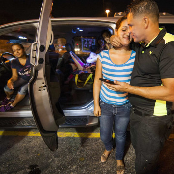 Image: Cuban migrant Mailin Perez  embraces with her husband Jose Caballero after arriving via Mexico at a bus station in Austin