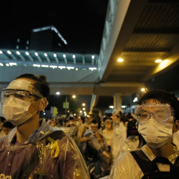 Image: Protesters wearing masks and goggles gather outside the government headquarters in Hong Kong