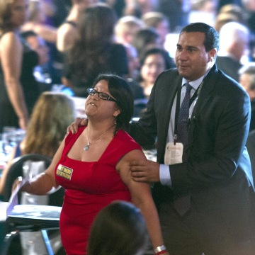 Image: A woman who was shouting at President Barack Obama as he addressed the Congressional Hispanic Caucus Institute's 37th annual awards gala is removed