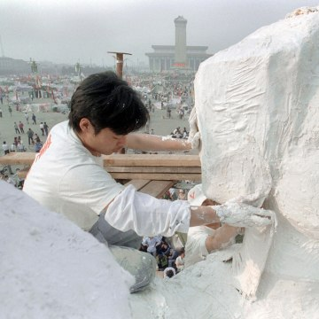 """Image: A Chinese student plasters the neck of the """"Goddess of Democracy"""" in Tiananmen Square on May 30, 1989"""
