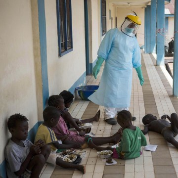 Image: A health official dressed in protective gear examines children suffering from the Ebola virus