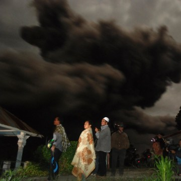 Image: Residents gather outside their houses in Karo district as dark giant ash clouds, seen in the background, rise from the crater of Mount Sinabung