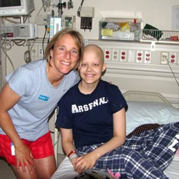 Annika Dybevik, 18, in her hospital bed being visited by coach Amy Griffin.