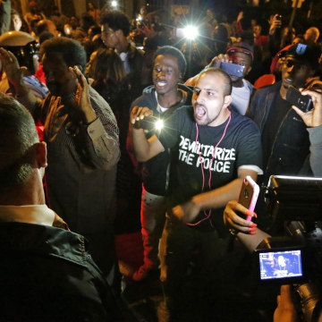Image: Crowds confront police near the scene in south St. Louis where a teen was fatally shot by an off-duty police officer
