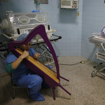 """Image: A member of """"El Sistema"""" plays on a harp, as part of its """"New Members"""" program, next to a newborn baby at a public maternity hospital in Caracas"""