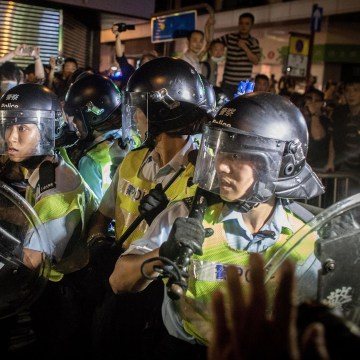 Image: Pro-democracy protesters push police back as they break down barricades and take back streets in Mong Kok on Oct. 18