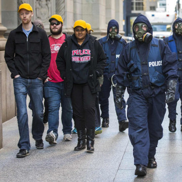 Image: Toronto Police officers wearing gas masks walk down King Street in the heart of the financial district during a mock crisis response exercise in Toronto