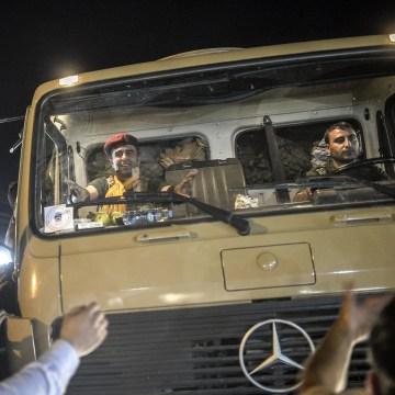 Image: A peshmerga fighter sitting in a truck gestures as Kurds in Turkey greet peshmerga convoys in Viransehir, in Turkey's southeastern Sanliurfa province