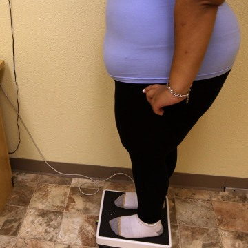 Image: Overweight woman stands on a scale