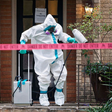 Image: A member of the CG Environmental HazMat team disinfects the entrance to the residence of a health worker at the Texas Health Presbyterian Hospital who has contracted Ebola in Dallas, Texa