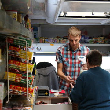 Image: Mark Reiche helps a customer inside his family's rolling supermarket