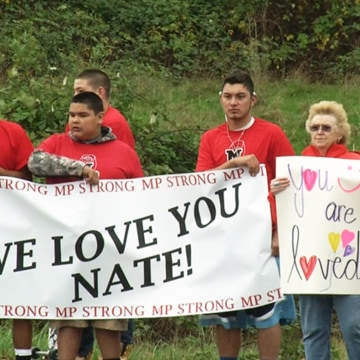 Image: People with banners welcome home Marysville shooting victim Nate Hatch at the Tulalip Indian Reservation in Washington