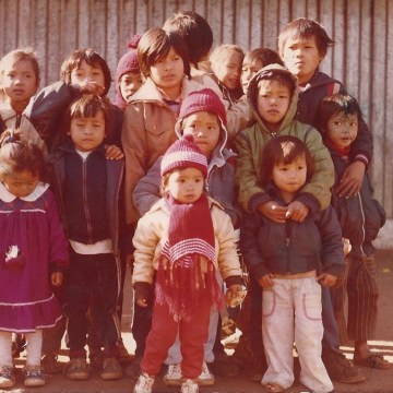 Monica Phromsavanh (front center) seen wearing a red hat and red scarf, with friends from the Laotian community inside a refugee camp in Argentina in 1986.