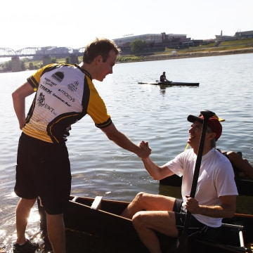 Image: U.S. Sen. Rob Portman is greeted by his son Will, 20 after finishing the annual Cincinnati event, Paddlefest