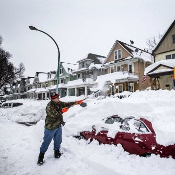 Image: Thomas Wisniewki digs his car out of snow following a massive snow storm in Buffalo
